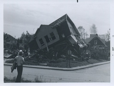Man Looking at a Destroyed House